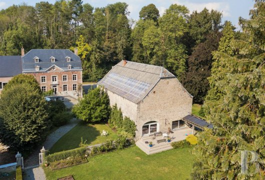 A manor house and its orangery on the side of a stream  in the Liège province's natural region of Condroz
